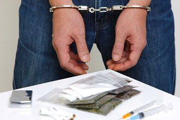Columbus, Ohio drug charges defense lawyer for man in handcuffs in front of drugs and drug paraphernalia